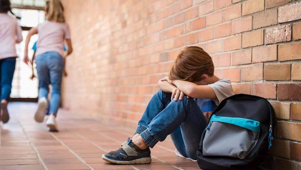 niño afligido por acoso y rechazo compañeros colegio