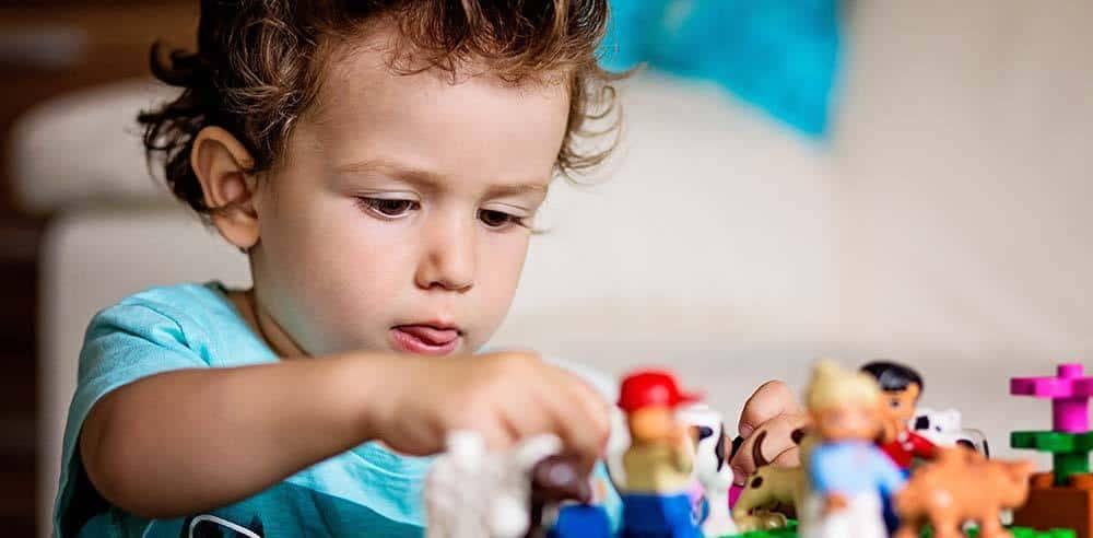 Niño jugando con figuras en terapia infantil