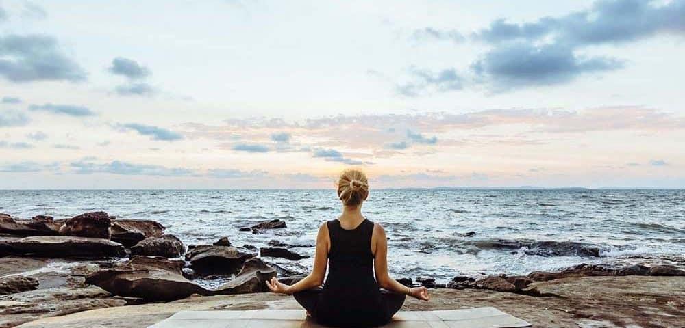 mujer meditando en playa